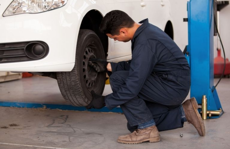 Image of an auto mechanic checking a car's tires
